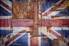 Corrugated Iron United Kingdom Flag. An abstract background image of rusty corrugated iron sheets overlapping to form a wall or fence with an aged flag of Royalty Free Stock Images