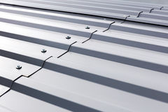 Corrugated metal cladding on industrial building roof. Gray corrugated metal cladding on industrial building roof Stock Photos