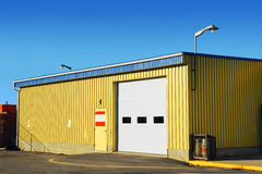 Corrugated metal siding arena. Industrial looking small garage covered with corrugated metal siding, with propane containers on one side and stored crates behind Royalty Free Stock Photography