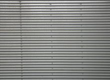 Corrugated metal wall, detail of a wall lined with metal, shiny steel royalty free stock photography
