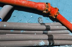 Corrugated pipes and a red pipe in digging in the road construct Stock Image