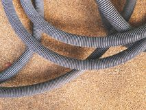 Corrugated Plastic Bellow Hoses on the Floor. Corrugated Plastic Bellow Hoses of Vacuum Cleaners on the Floor Stock Image