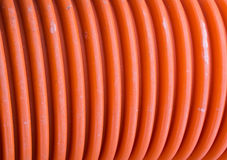 Corrugated plastic pipe of orange color. For passage of installations technological Stock Image