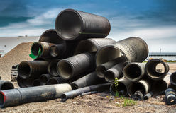 Corrugated plastic pipe. Pile of black plastic corrugated plumbing pipe Stock Photo