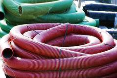 Corrugated plastic pipes. Coil of red and green plastic corrugated plumbing pipes Royalty Free Stock Image