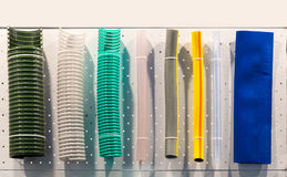 Corrugated plastic tubes and rubber water hoses. Plumbing shop showcase Royalty Free Stock Photos