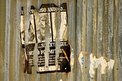 Corrugated Poster. An old spanish or mexican poster peeling off the side of a corrugated building Stock Images