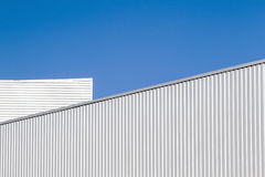 Corrugated sheet metal wall and roof against blue sky. Modern warehouse or storage. Industrial look. Outdoor. Digital. Corrugated sheet metal wall and roof royalty free stock photo
