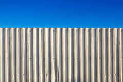 Corrugated white metal fence. And blue sky stock photo
