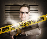 Corrupt business man behind crime scene tape. Corrupt business man in prisoner bondage standing on lined police wall behind crime scene tape Stock Image