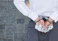 Corrupt businessman in handcuffs holding money against wall Royalty Free Stock Image