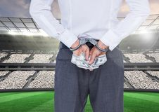 Corrupt businessman in handcuffs holding money at stadium Stock Images