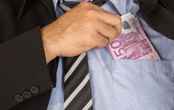 Corrupt. Businessman a putting money in his pocket Royalty Free Stock Photography