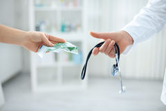 Corrupt doctor taking bribe from patient Stock Image