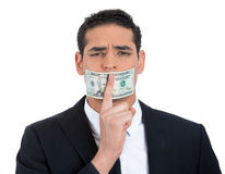 Corrupt guy in black suit with twenty dollar bill taped to mouth, showing shhh sign Stock Photography