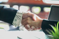 Corrupted businessman sealing the deal with a handshake and receiving a bribe money, anti bribery and corruption concepts stock images