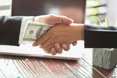 Corrupted businessman sealing the deal with a handshake and receiving a bribe money, anti bribery and corruption concepts.  stock photography