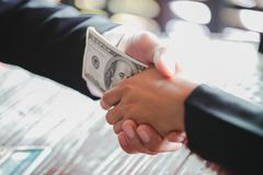 Corrupted businessman sealing the deal with a handshake and receiving a bribe money, anti bribery and corruption concepts.  royalty free stock photography
