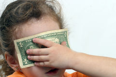 Corrupted innocence. Small girl with eyes covered with money. for stories or concepts about minor corruption Royalty Free Stock Photos