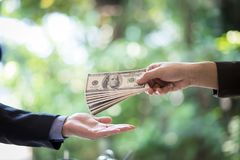 Corrupted two businessman sealing the deal with a handshake and receiving a bribe money. Hands passing money corruption bribery Royalty Free Stock Images
