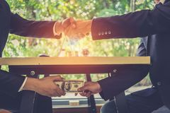 Corrupted two businessman sealing the deal with a handshake and receiving a bribe money. Hands passing money under table corruption bribery Royalty Free Stock Photography