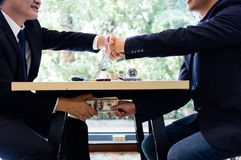 Corrupted two businessman sealing the deal with a handshake and receiving a bribe money. Hands passing money under table corruption bribery. Corruption concept Stock Photography