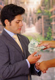 Corrupted young businessman accepting some money from a crook Stock Photography