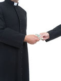 Corruptible priest. Catholic priest receiving bribe from businessman Royalty Free Stock Photos