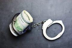 Corruptieconcept met Amerikaanse dollarrekeningen in metaaldiehandcuffs op donkere achtergrond wordt geïsoleerd stock afbeeldingen