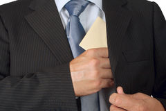 Corruption. Businessman putting an envelope in his jacket pocket - concept of bribe royalty free stock photos