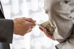 Corruption and bribery concept. Businessman or politician taking bribe from a female colleague handing him Euro money from behind her back. Conceptual of Royalty Free Stock Photography