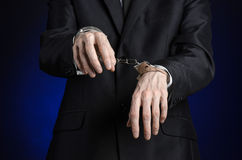 Corruption and bribery theme: businessman in a black suit with handcuffs on his hands on a dark blue background in studio isolated Royalty Free Stock Photos