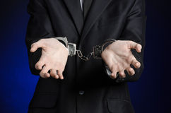 Corruption and bribery theme: businessman in a black suit with handcuffs on his hands on a dark blue background in studio isolated Stock Photo