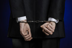 Corruption and bribery theme: businessman in a black suit with handcuffs on his hands on a dark blue background in studio isolated Stock Image