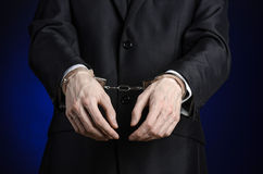 Corruption and bribery theme: businessman in a black suit with handcuffs on his hands on a dark blue background in studio isolated Royalty Free Stock Image