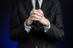 Corruption and bribery theme: businessman in a black suit with handcuffs on his hands on a dark blue background in studio isolated Stock Photography