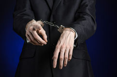 Corruption and bribery theme: businessman in a black suit with handcuffs on his hands on a dark blue background in studio isolated Royalty Free Stock Photography