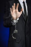 Corruption and bribery theme: businessman in a black suit with handcuffs on his hands on a dark blue background in studio isolated Royalty Free Stock Images