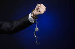 Corruption and bribery theme: businessman in a black suit with handcuffs on his hands on a dark blue background in studio isolated Stock Photos
