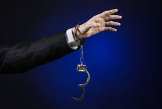 Corruption and bribery theme: businessman in a black suit with handcuffs on his hands on a dark blue background in studio isolated Stock Images