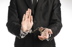 Corruption and bribery theme: businessman in a black suit with handcuffs on his hands on a white background in studio isolated Royalty Free Stock Photography