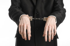Corruption and bribery theme: businessman in a black suit with handcuffs on his hands on a white background in studio isolated Royalty Free Stock Photos