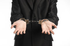 Corruption and bribery theme: businessman in a black suit with handcuffs on his hands on a white background in studio isolated Royalty Free Stock Photo