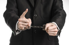 Corruption and bribery theme: businessman in a black suit with handcuffs on his hands on a white background in studio isolated Stock Photography