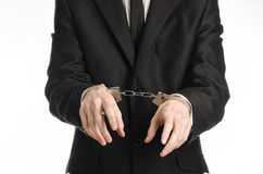Corruption and bribery theme: businessman in a black suit with handcuffs on his hands on a white background in studio isolated Stock Images