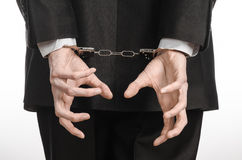 Corruption and bribery theme: businessman in a black suit with handcuffs on his hands on a white background in studio isolated Stock Photo