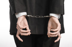 Corruption and bribery theme: businessman in a black suit with handcuffs on his hands on a white background in studio isolated Stock Photos