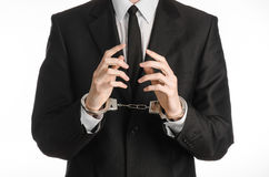 Corruption and bribery theme: businessman in a black suit with handcuffs on his hands on a white background in studio isolated Royalty Free Stock Images