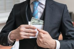 Corruption concept. Businessman is hiding letter full of money or bribe in suit jacket Stock Photos