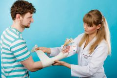 Female doctor bandaging male hand. Stock Photography